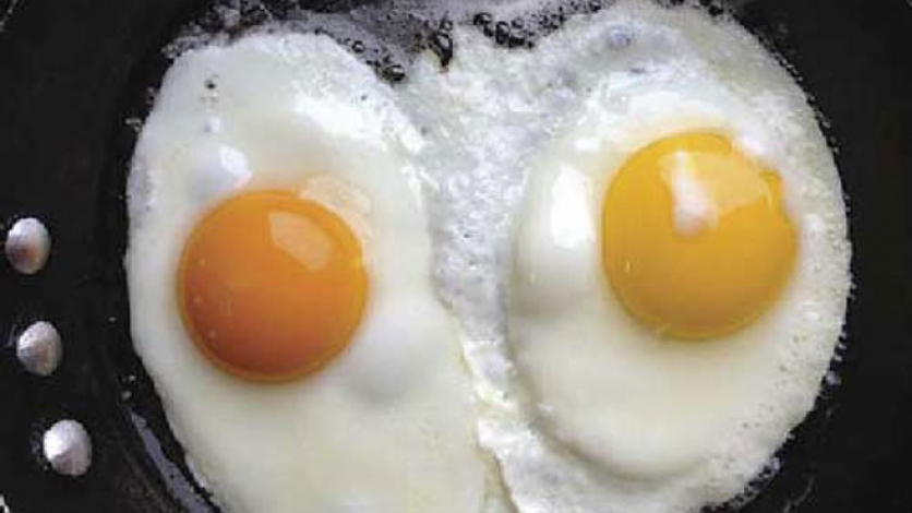 Two fried eggs, one with a yellow yolk, the other an orange yolk