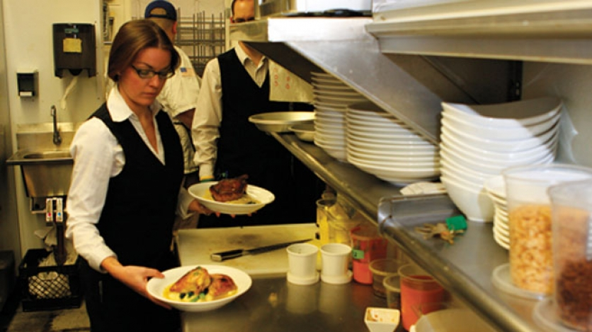 servers grab plates in the kitchen of Pain d'Avignon