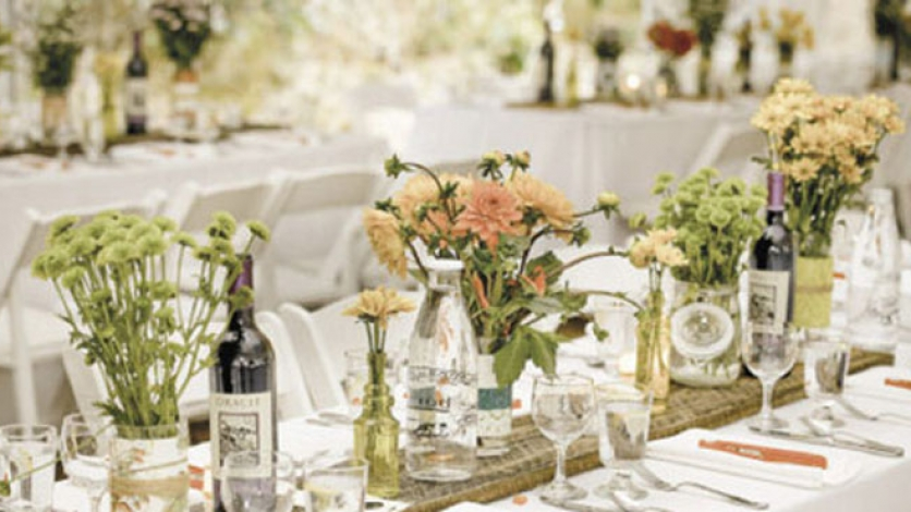 a beautiful table arrangement features fresh flowers, crystal glasses, and bottles of wine