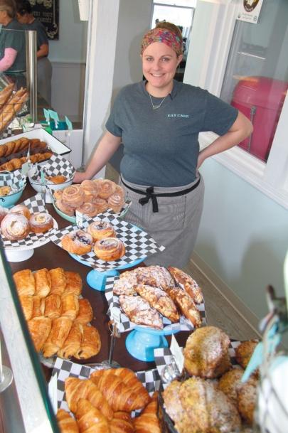 Danielle Nettleton, owner/baker of Eat Cake 4 Breakfast, alongside a display of her baked goods.